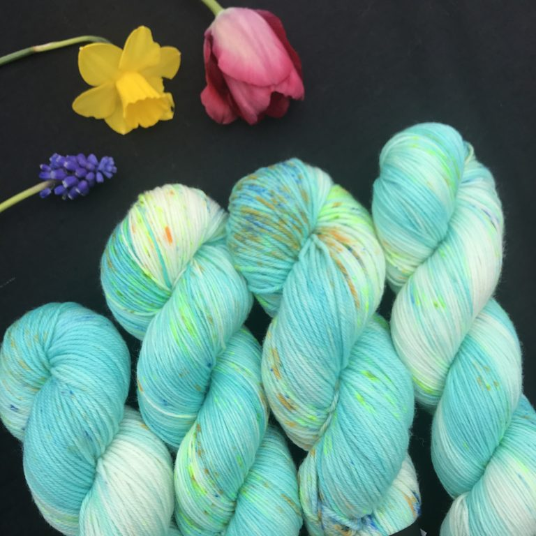 green toned aqua yarn with white flashes and speckles of bright green, deep yellow and blue