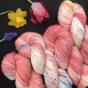 coral pink yarn with white flashes and speckles of yellow blue and pink