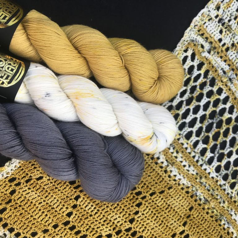 a crochet shawl is laid flat, the pattern in the Hotel of Bees shawl and shows honeycomb sections. there are three skeins laid on top, one grey, one mustard and one natural with grey and mustard speckles