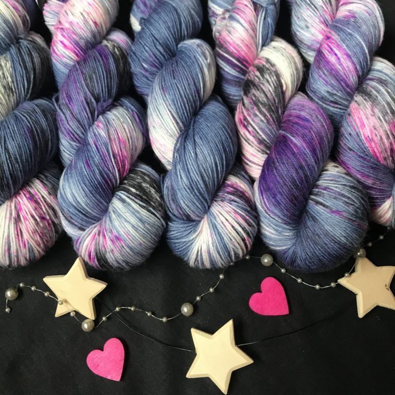 deep navy blue yarn with white flashes and lots of black, pink and purple speckles