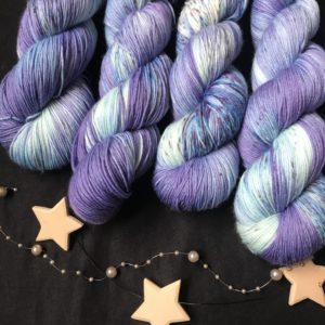 purple blue yarn, with darker and lighter areas and flashes of white, speckled with blues and a hint of pink