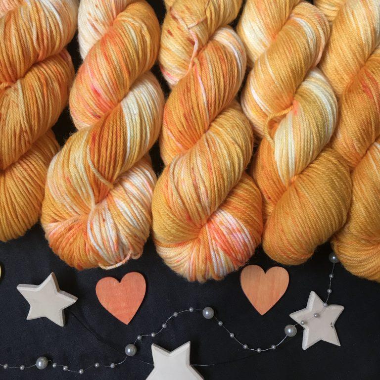 golden yellow/orange yarn with white flashes and darker orange speckles