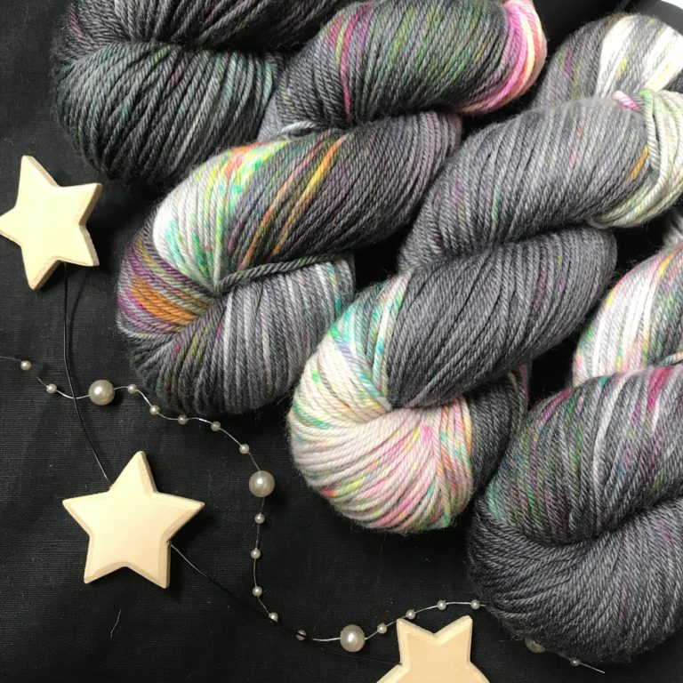 black yarn with white flashes and neon speckles of green. pink, yellow and orange.