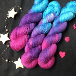 regular repeating yarn moving from deep magenta pink, to Cadbury purple, to a bright carribean blue. The colours flow from the front of the twisted skein to the back.