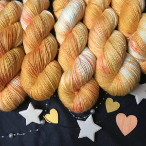 golden yellow/orange yarn with a hint of sparkle visible. there are white areas, and darker orange speckles