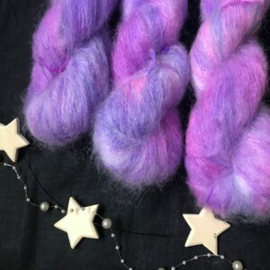 neon purple fluffy yarn with darker and lighter shades, on a black background