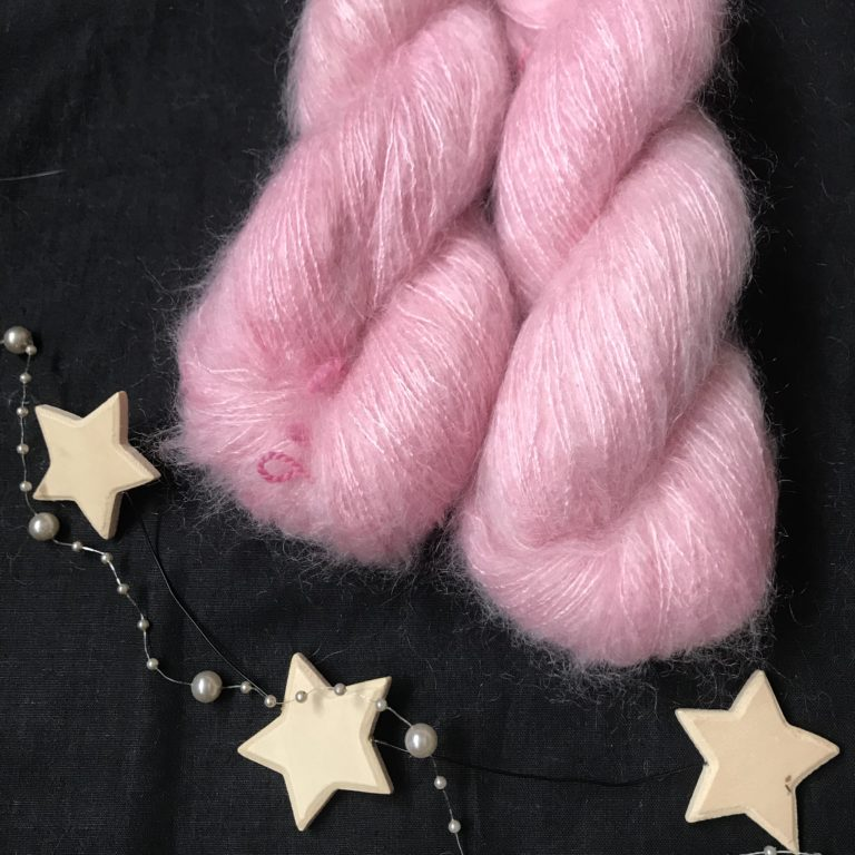 candy pink fluffy yarn on a black background. it has a slight sheen to it.