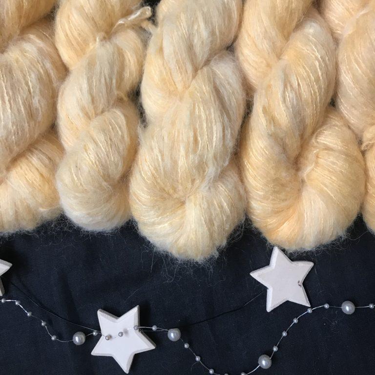 yellowy orange fluffy yarn, in a soft shade, on a black background