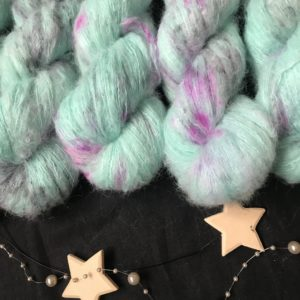 aqua green fluffy yarn with flashes of neon pink and black on a black background