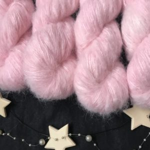 soft baby pink fluffy yarn on a black background