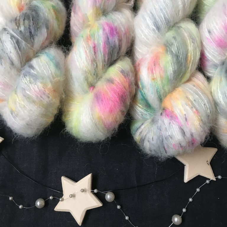 fluffy natural base with speckles of neon pink, neon orange, neon yellow, aqua and black on a black background.