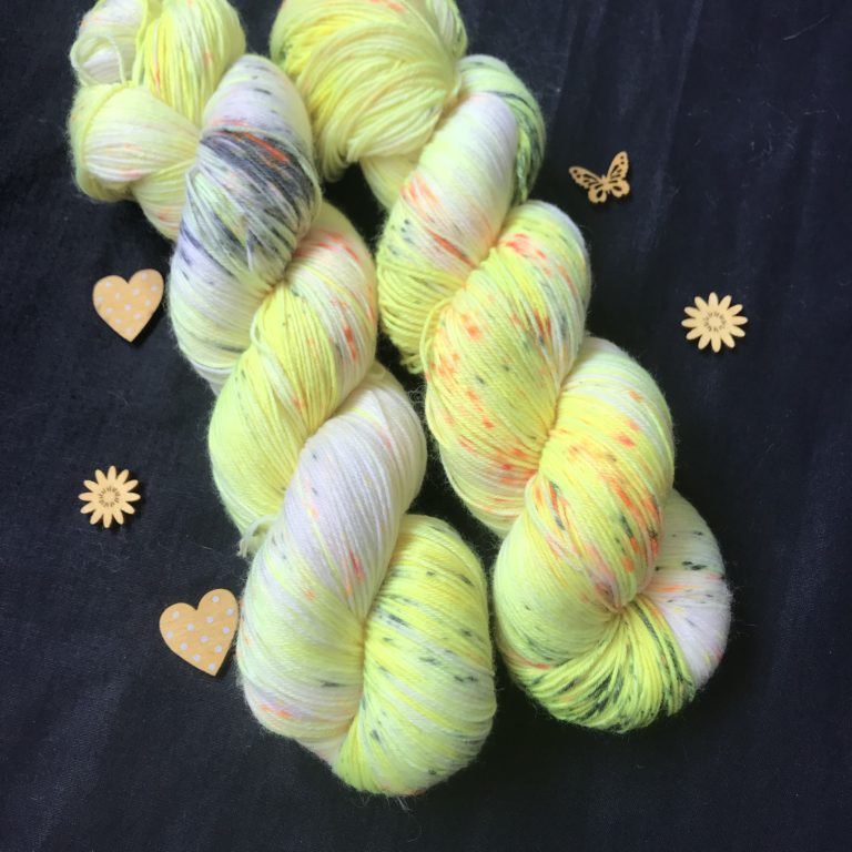 neon yellow yarn with undyed areas and speckles of orange and black