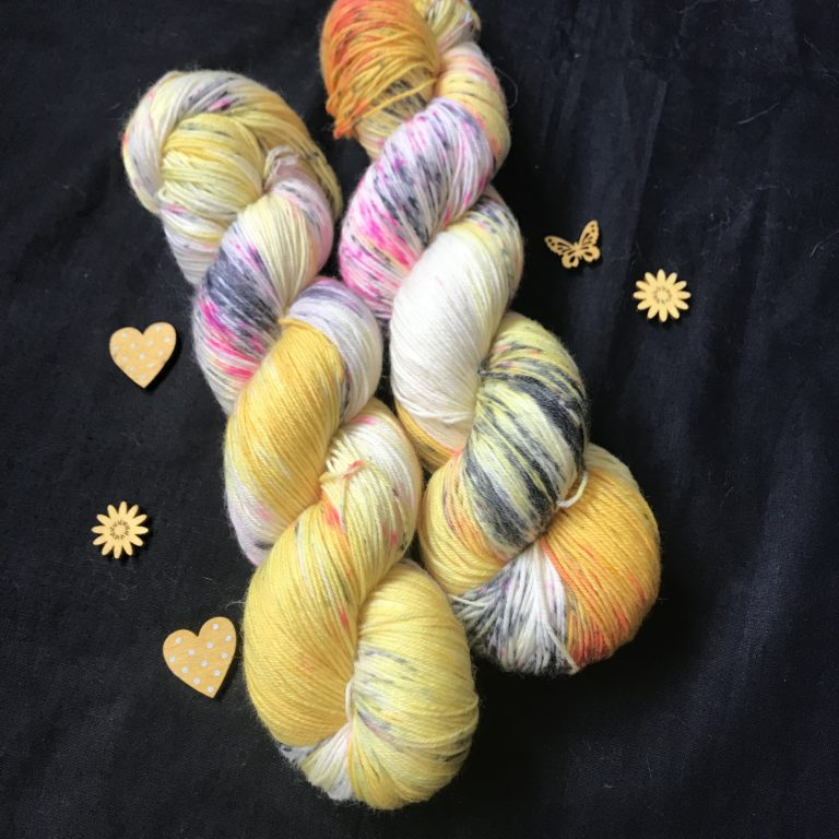 daffodil yellow yarn with undyed areas and speckles of black and pink