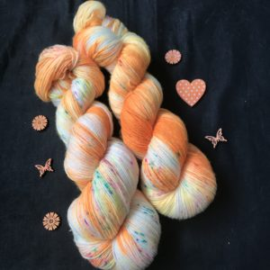 neon orange yarn with undyed areas, speckled with pink, blue and yellow