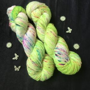 neon green yarn with some white flashes, speckled with blues and pinks
