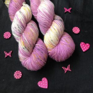 soft pink yarn with undyed areas and speckles of yellow and black