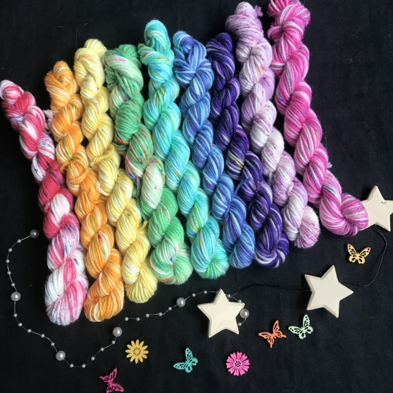 set of 9 mini skeins each with a different base colour and speckles. They are in rainbow order (red, orange, yellow. green, aqua, blue, purple, lilac, pink)
