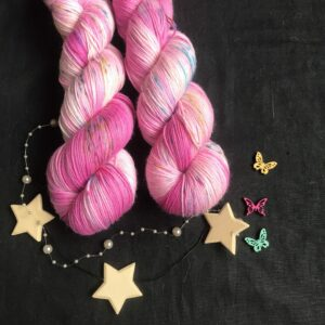 mid range pink and white marbled yarn with blue and yellow speckles on a black background