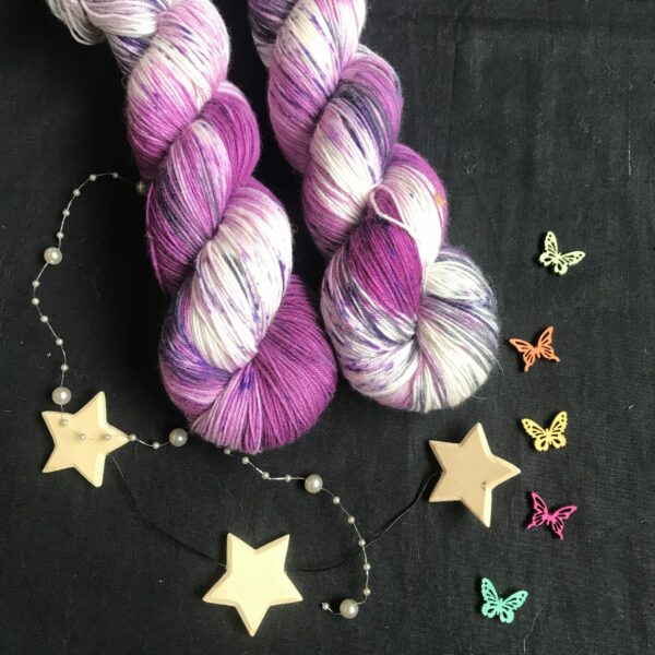deep raspberry pinky/purple yarn, with undid areas, speckled with purples and black