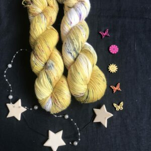mustard coloured yarn, with areas undyed, speckled with black and red