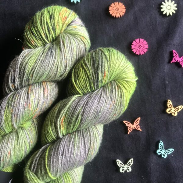 two skeins of silvery yak with patches of flare yellow and speckles of orange and black on a black background