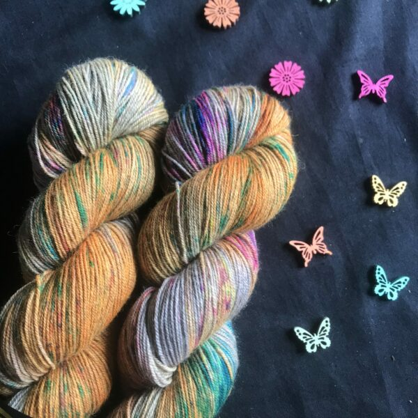 rich neon orange skeins, with patches of undyed silver yak, speckled with pinks, blues and greens on a black background
