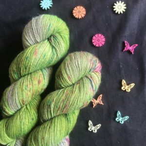 neon green and undyed silver yak skeins with speckles of purple, blue and green on a black background