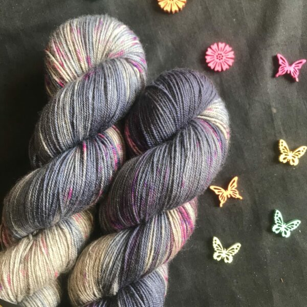 skeins showing undyed silverish yak, with rich blue-purple patches and pops of black and neon purple, on a black background with pink flower cut outs