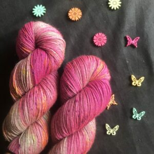 rich neon pink yarn, with pops of purple, orange and yellow. unyed sections of the yarn blend yarn are a silverish colour, and the yarn has a noticable sheen