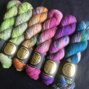 a set of 6 yak blend yarns, in a neon rainbow, on a black background