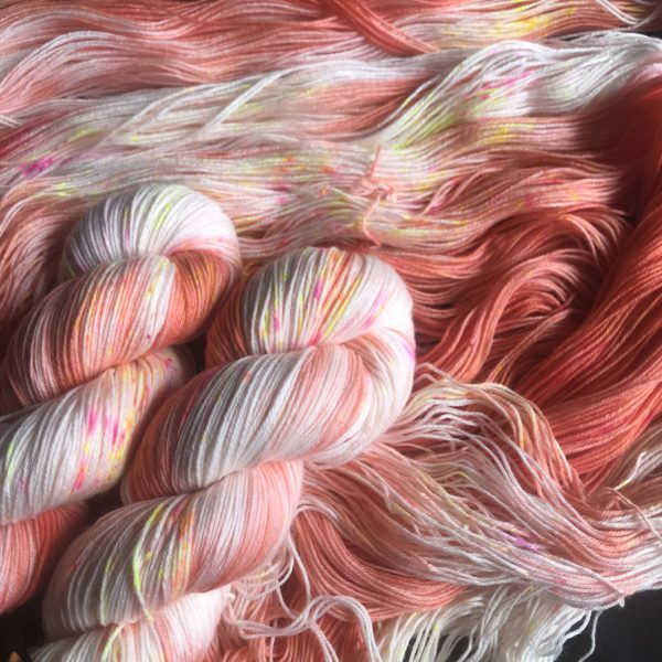 rich peach and white yarn, untwisted with two skeins on top, speckled with orange and neon pink