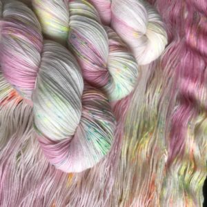 soft pink and white yarn with speckles of blue, yellow and orange. one skein is laid out with 3 more twisted on top