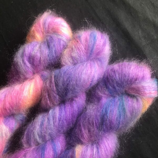 neon purple fluffy yarn with flashes of blue, orange and yellow on a black background