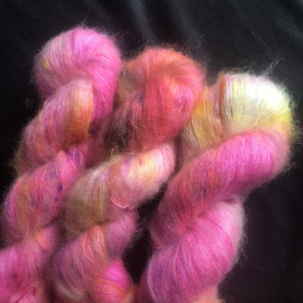 fluffy neon pink skeins, with flashes of white, purple, orange and yellow, on a black background