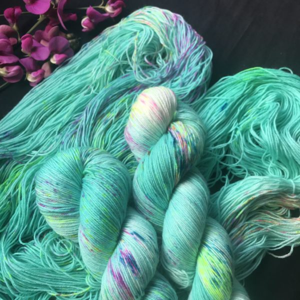 a skein of deep aqua yarn, with two skeins twisted on top. the yarn is speckled with pinks, blues and neon yellows.