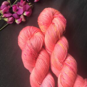 strong salmon pink skeins speckles with pink and yellow, on a black background