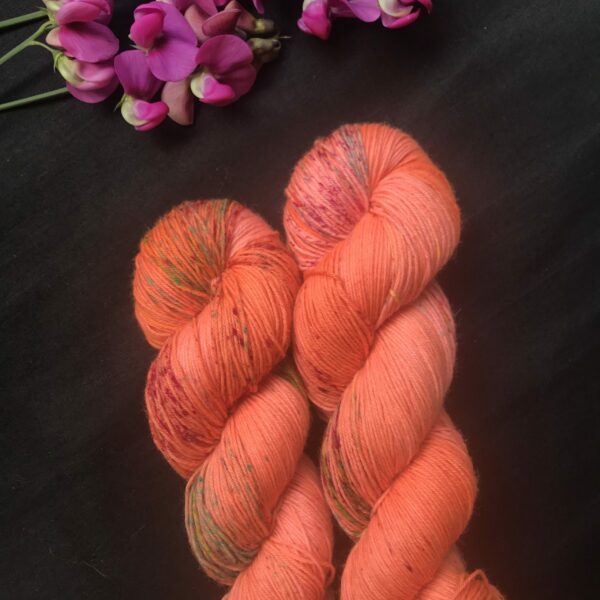 a black background with magenta sweet peas at the top. two skeins of bright orangey/coral yarn are shown, speckled with pink and green
