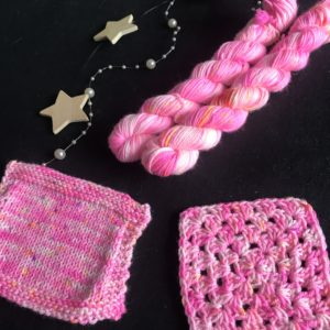 neon pink mini skeins on a black background. Knit and crochet samples show the pink yarn worked up with white patches and speckles of yellow, orange and purple