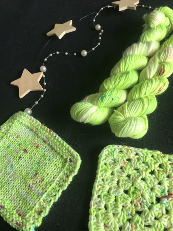 neon green minis on a black background. the yarn has small white flashes and is speckled with pinks and blues. knit and crochet swatches show the yarn worked up