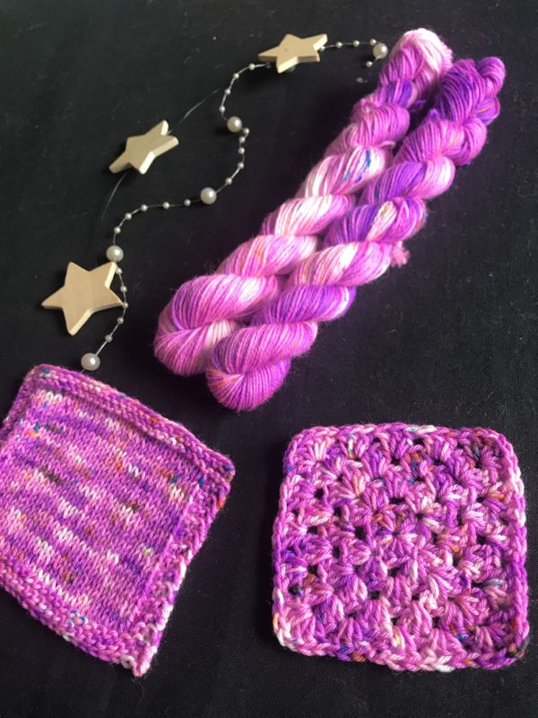 neon purple mini skeins on a black background. samples show the yarn worked up with white flashes and speckles of orange, blue and yellow