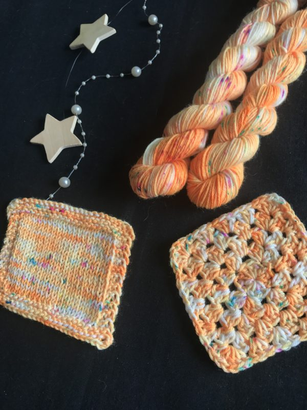 neon orange mini skeins on a black background with white flashes and neon speckles of blue, pink and yellow. swatches show the yarn knitted and crocheted.