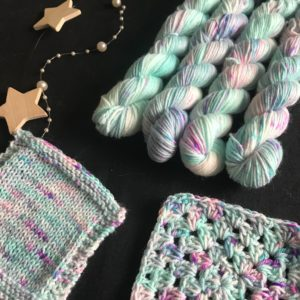 mini skeins on a back background with swatches to the front. the yarn has a pink and aqua base with flashes of white and soft purple, speckled with greens and neon purples.