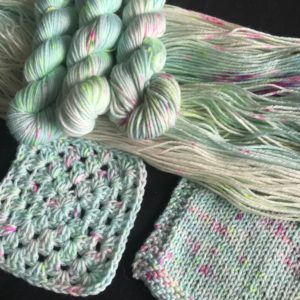 opened skein with mini skeins on top and swatches to the front. the yarn is soft blue with white flashes and speckles of neon pink, green and aqua.
