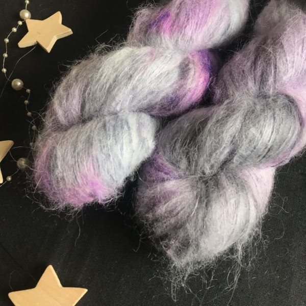 fluffy yarn on a black background. the yarn is grey blue base with flashes of neon purple and darker purple