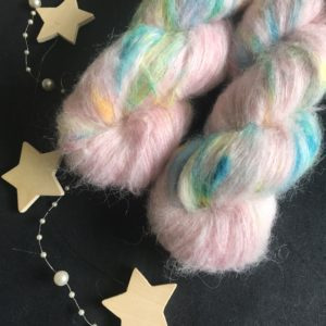 fluffy yarn on a black background. the yarn is pale pink with flashes of blue, neon yellow and neon orange