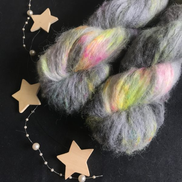 fluffy yarn on a black background. the yarn is dark grey/black base with flashes of neon pink, aqua, neon yellow and neon orange.