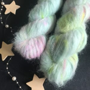 fluffy yarn on a black background. the yarn is delicate soft blue with speckles of neon pink, neon green and aqua