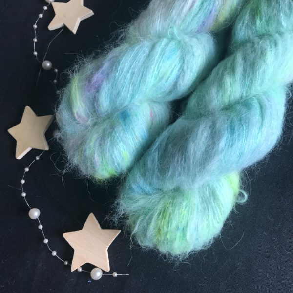 fluffy yarn o a black background. the yarn is aqua base with speckles of neon pink, blue and neon yellow