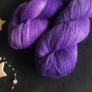 cadbury purple single spun lace weight yarn on a black background