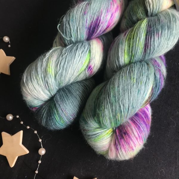 single spun lace yarn on a black background. the yarn is dyed teal blue with white flashes and speckles of neon purple, aqua and neon green